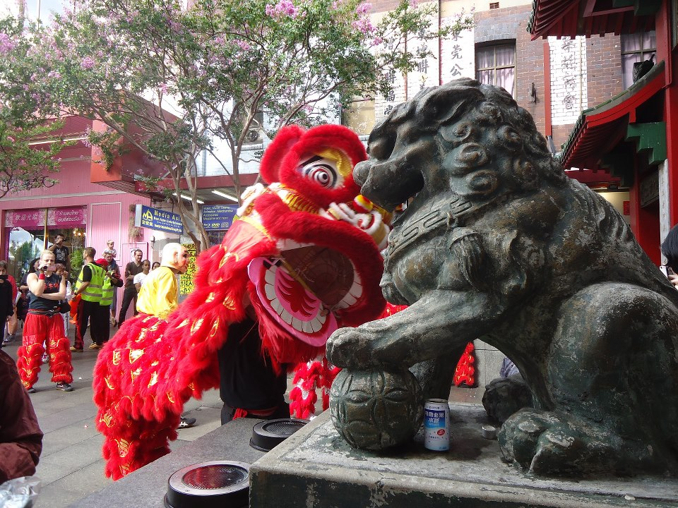 Chinese lion salutes stone lion at Sydney Chinatown gate